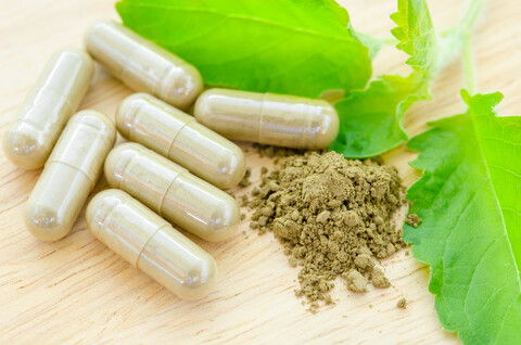 herbal medicine powder and capsules with green organic herb leaves on wooden background.
